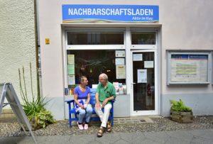 Foto mit zwei Personen auf blauer Bank des Nachbarschaftsladens